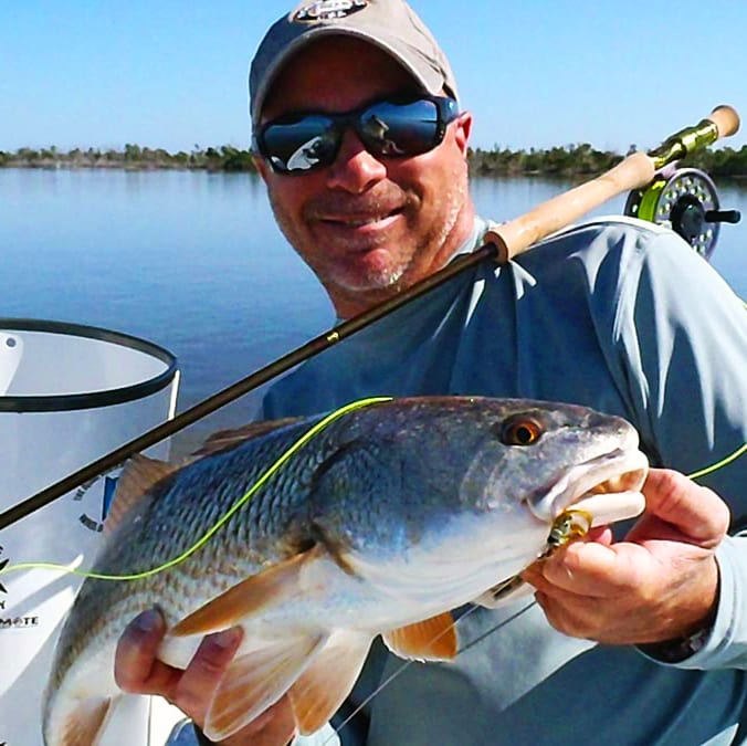 Angler holding a redfish caught on fly rod in Boca Grande. Florida